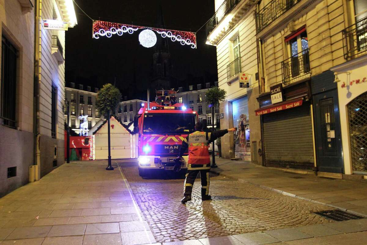 A rescue worker directs a fire brigade vehicle after a van crashed into a French Christmas market in Nantes, western France, Monday, Dec. 22, 2014. French authorities urged calm after a series of attacks across the country left dozens of people injured, and said there was no evidence the attacks were connected by any terrorist motive. In the latest incident, 11 people were injured after a driver crashed his van into a crowded Christmas market in western France Monday evening. The driver then stabbed himself several times and is among five people hospitalized in serious condition, authorities said. (AP Photo/Laetitia Notarianni)