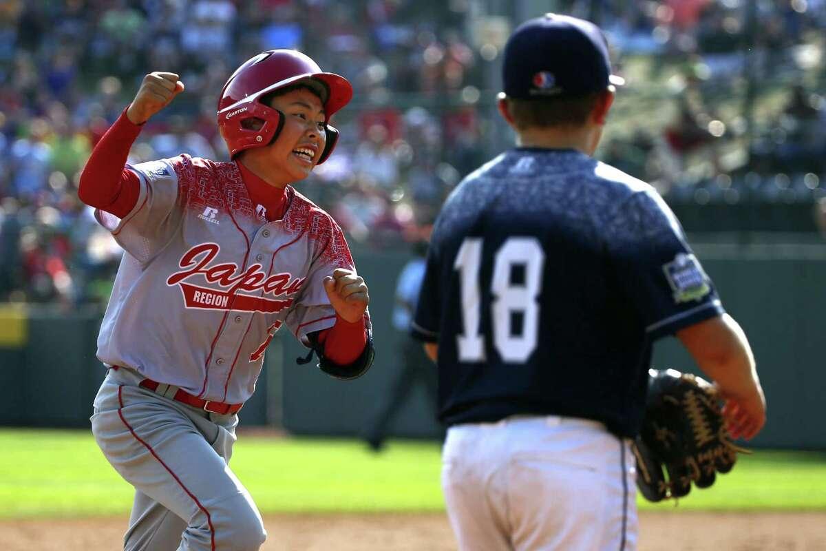 Japan's Masafuji Nishijima, left, rounds third past Dylan Rodenhaber (18) after hitting a three-run home run Sunday.