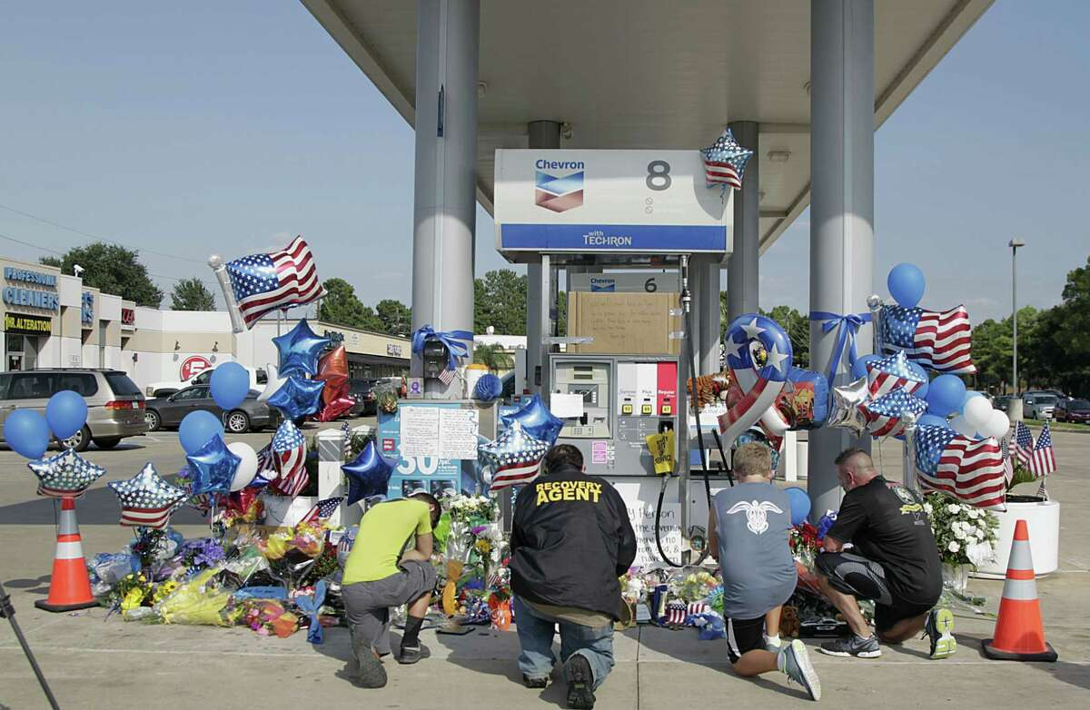 Mourners gather at a gas station in Houston on Aug. 29, 2015 to pay their respects at a makeshift memorial for Harris County Sheriff's Deputy Darren Goforth who was shot and killed while filling his patrol car. On Saturday, prosecutors charged Shannon J. Miles with capital murder in the Friday shooting.