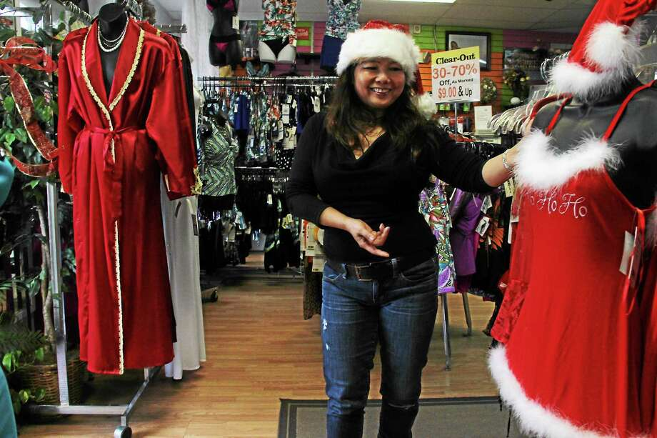 Tina Fine, of Tina's Fine Lingerie & Swimsuits, located at 394 Main St., shows off a red satin chemise that promises to make someone's winter holidays cozy. Photo: Kathleen Schassler — THE Middletown Press  / Kathleen Schassler All Rights