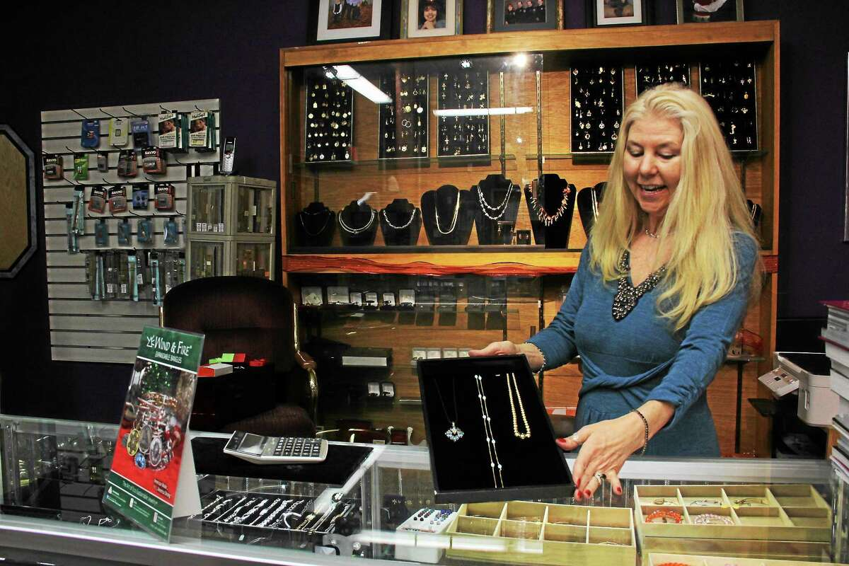 Kathleen Schassler — THE Middletown Press Pamela Feola, owner of PJ Jewelers in the Main Street Marketplace, examines some of the unique gold pieces available at the shop.