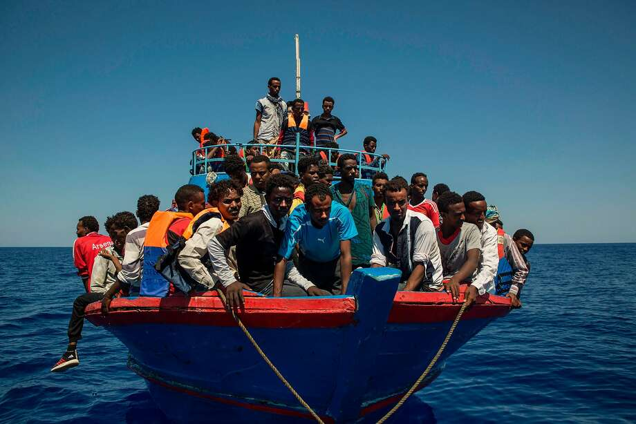 Refugees wait to be picked up by the rescue ship Aquarius in the Mediterranean Sea off the coast of Libya this month. The Libyan coast guard has recently increased its aggression. Photo: ANGELOS TZORTZINIS, AFP/Getty Images