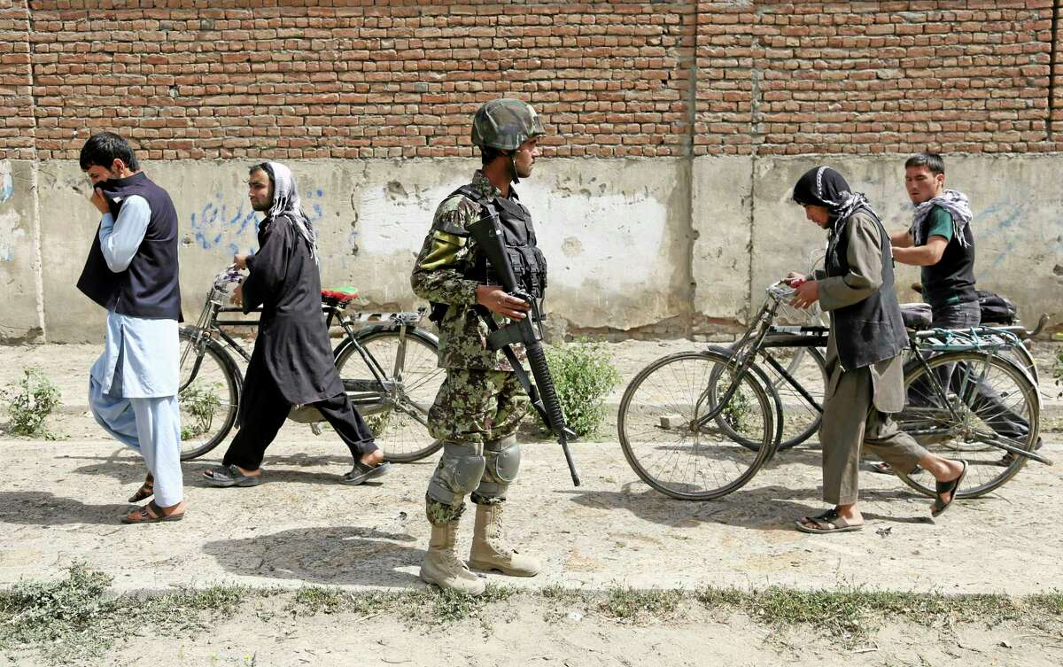Afghanistan's National Army (ANA) soldier, center, stands guard at the site of a suicide attack in Kabul, Afghanistan, Wednesday, July 2, 2014. A suicide bomber attacked an air force bus in Kabul, early Wednesday, killing at least four people, security officials said. (AP Photo/Rahmat Gul)