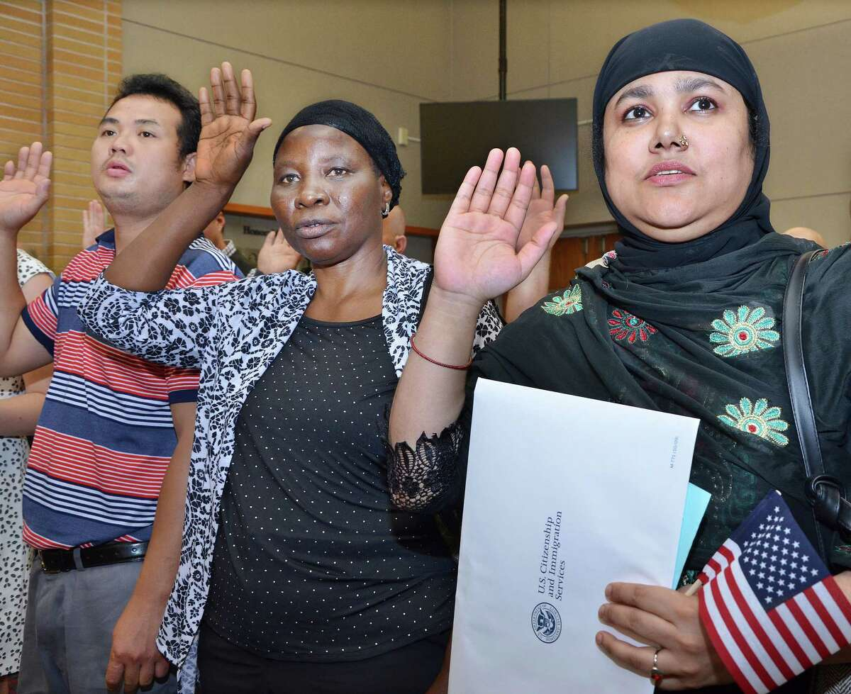 New citizens, Bridgeport resident Amina Begum, of Bangladesh, right, and New Haven resident Zainab Ahmed Saido, of Nigeria, raise their right hands as Judge Stefan Underhill administers the Oath of Allegiance at the Naturalization Ceremony at Middletown City Hall Wednesday afternoon.