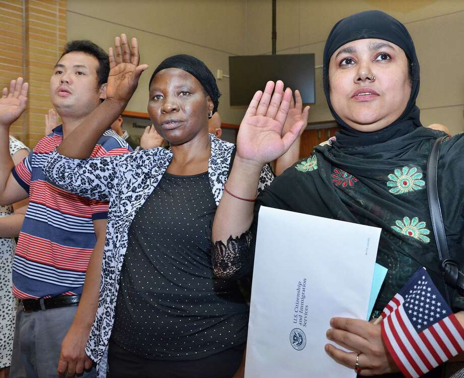 New citizens, Bridgeport resident Amina Begum, of Bangladesh, right, and New Haven resident Zainab Ahmed Saido, of Nigeria, raise their right hands as Judge Stefan Underhill administers the Oath of Allegiance at the Naturalization Ceremony at Middletown City Hall Wednesday afternoon. Photo: Catherine Avalone — The Middletown Press