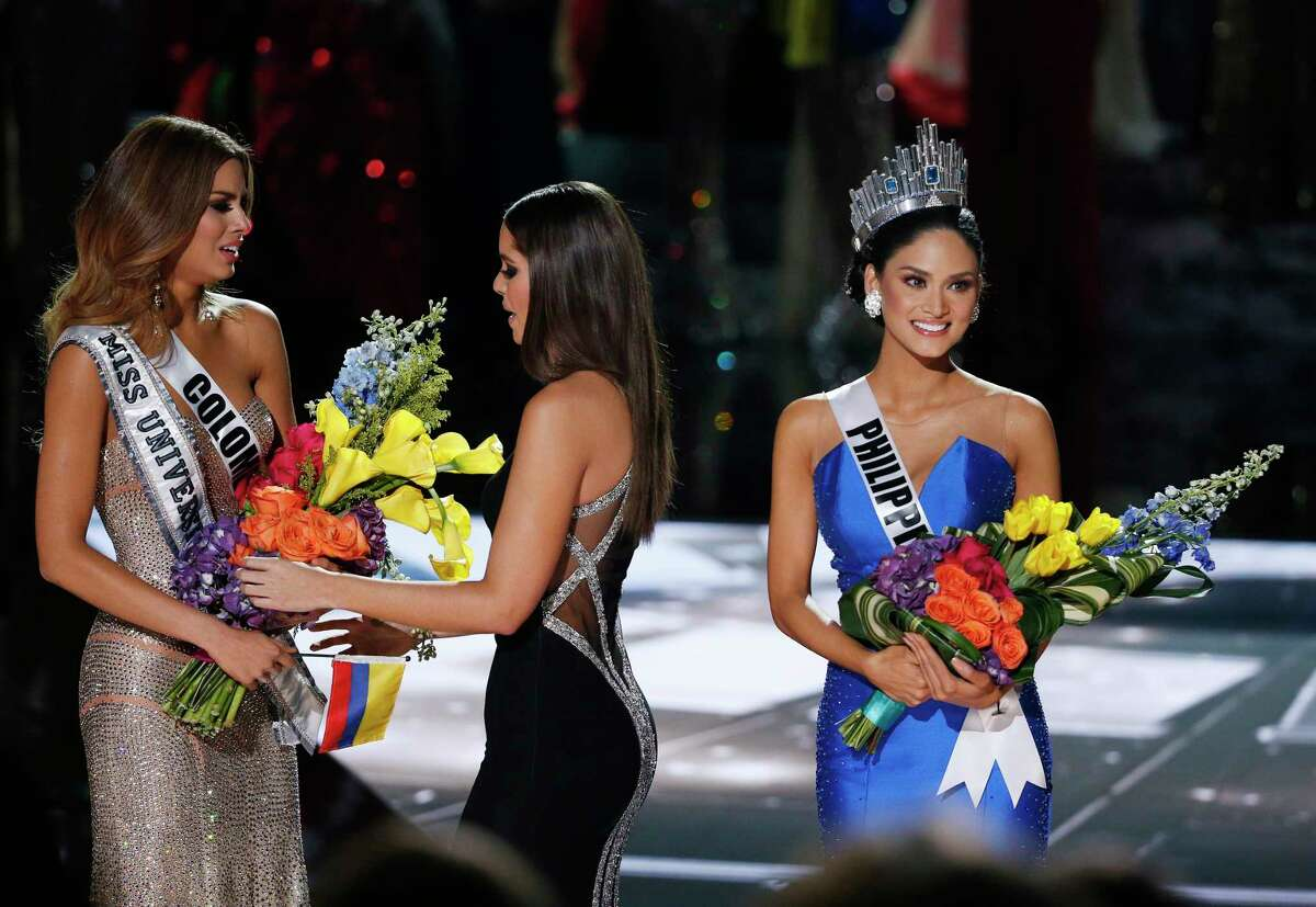 Former Miss Universe Paulina Vega, center, takes away the flowers and sash from Miss Colombia Ariadna Gutierrez, left, before giving it to Miss Philippines Pia Alonzo Wurtzbach, right, at the Miss Universe pageant Sunday in Las Vegas. According to the pageant, a misreading led the announcer to read Miss Colombia Ariadna Gutierrez as the winner before they took it away and gave it to Miss Philippines