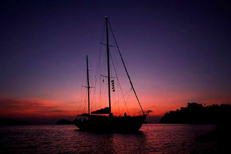 In this Feb. 9, 2014 photo, Meta IV, a $1 million yacht offering cruises among the reefs and islands, is silhouetted at sunset near Nyuang Wee Island, in Mergui Archipelago, Myanmar. Isolated for decades by the country's former military regime and piracy, the Mergui archipelago is thought by scientists to harbor some of the world's most important marine biodiversity and looms as a lodestone for those eager to experience one of Asia's last tourism frontiers before, as many fear, it succumbs to the ravages that have befallen many of the continent's once pristine seascapes. (AP Photo/Altaf Qadri) Photo: AP / AP