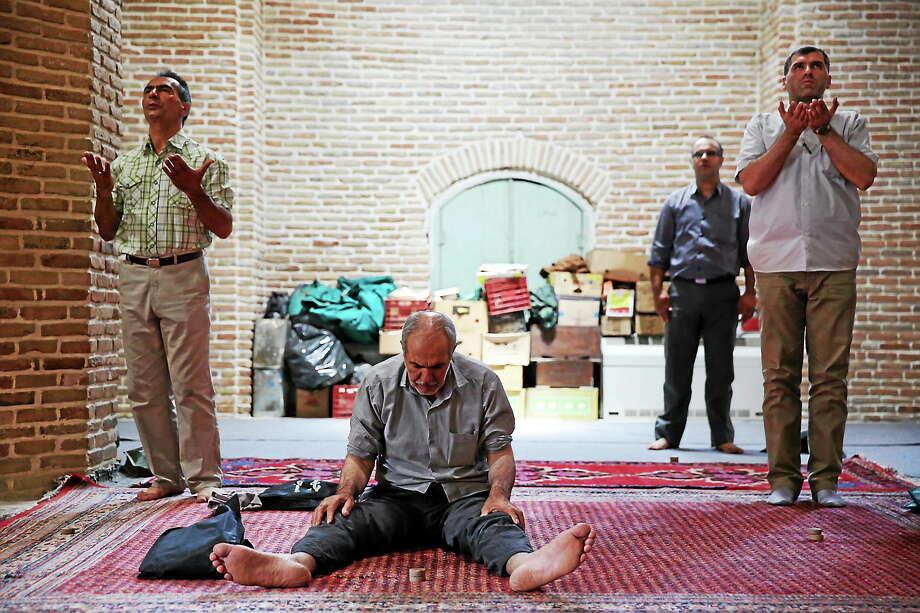 Iranian men pray at Jame mosque of Tehran's old main bazaar during the Muslim holy fasting month of Ramadan, Iran on July 1, 2014. Photo: AP Photo/Ebrahim Noroozi  / AP