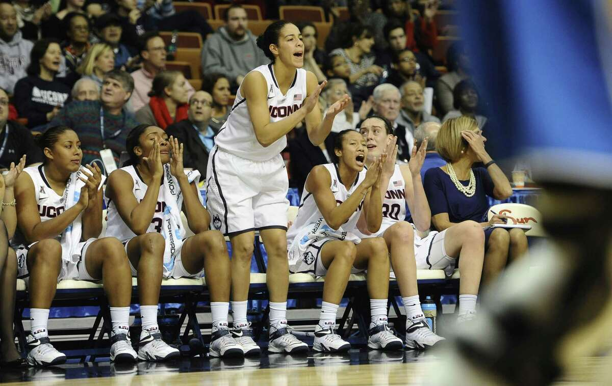 UConn's Kia Nurse, center, cheers on her team from the bench during Sunday's game.