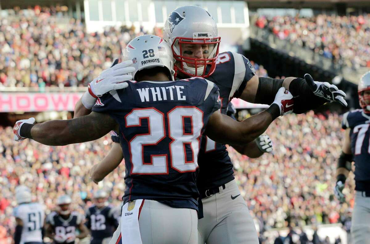 Patriots tight end Rob Gronkowski, rear, congratulates running back James White (28) on his touchdown in the first half Sunday.