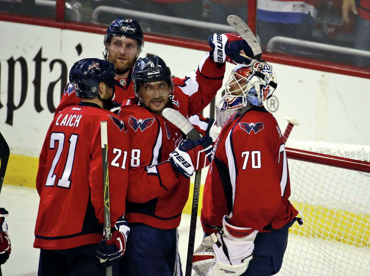 Capitals center Brooks Laich (21), defenseman Karl Alzner (27), left wing Alex Ovechkin (8) and goalie Braden Holtby (70) celebrate after a Game 5 win Thursday in Washington.