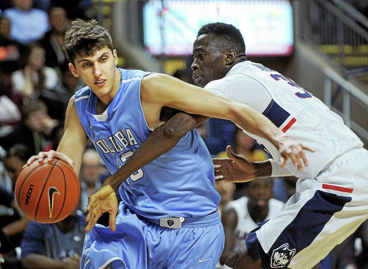 Columbia's Luke Petrasek, left, drives past UConn's Amida Brimah during the first half Monday.