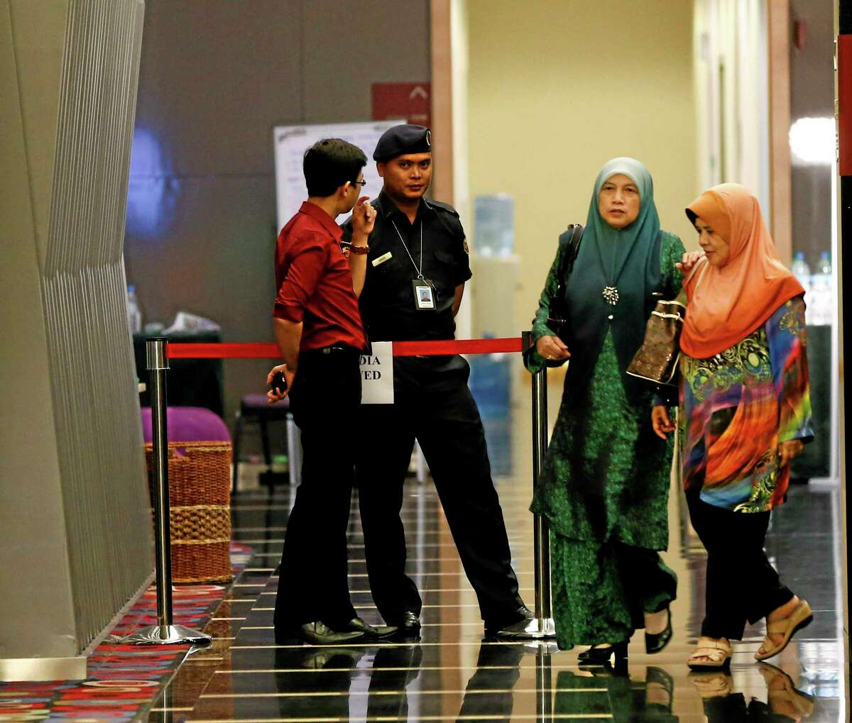 """Family members of passengers aboard a missing Malaysia Airlines plane walk out from a holding room as police stand guard at a hotel in Putrajaya, Malaysia, Thursday, March 20, 2014. An air search in the southern Indian Ocean for possible objects from the missing Malaysia Airlines plane described as the """"best lead"""" so far ended for the day without success Thursday but will resume in the morning, Australian rescue officials said. AP Photo/Vincent Thian"""