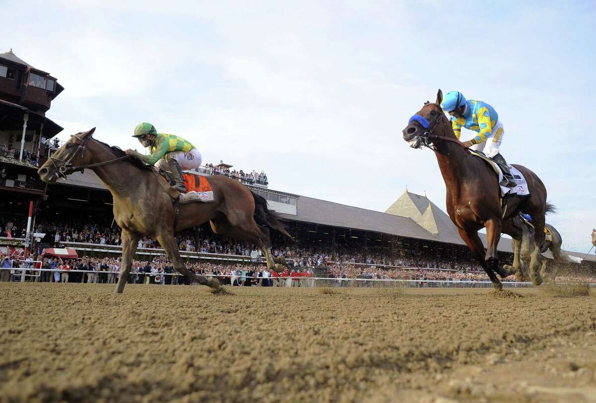 Keen Ice, left, with jockey Javier Castellano, moves past Triple Crown winner American Pharoah, with Victor Espinoza, to win the Travers Stakes Saturday at Saratoga Race Course in Saratoga Springs, N.Y.