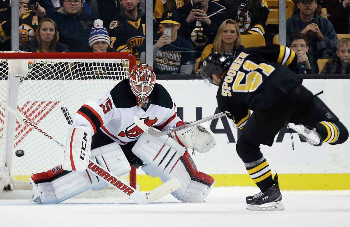 The Bruins' Ryan Spooner (51) scores on the Devils' Cory Schneider in a shootout during Sunday's game in Boston.