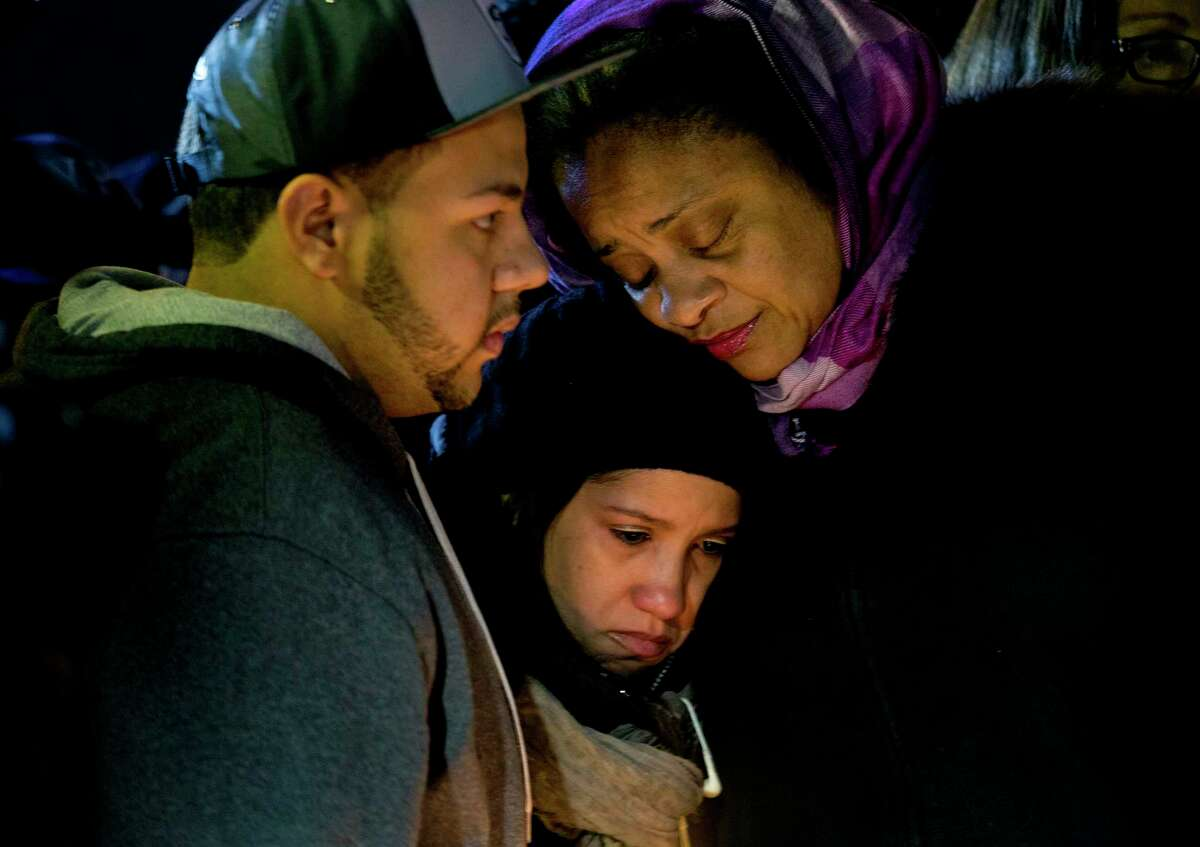 Mourners embrace Sunday, Dec. 21, 2014, during a vigil near the spot where two New York Police Department officers, sitting inside a patrol car the previous day, were shot by an armed man, killing them both. The assailant then went into a nearby subway station and committed suicide, police said.