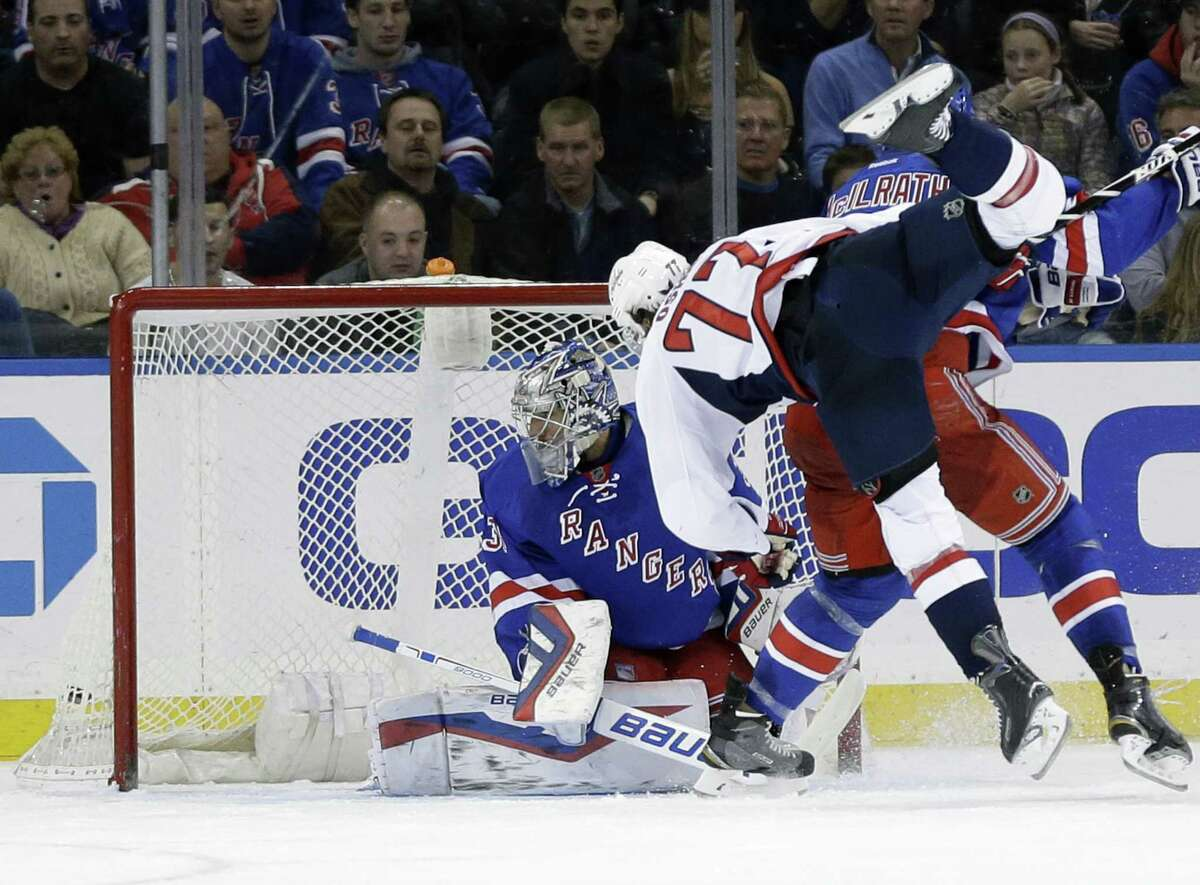 The Capitals' T.J. Oshie (77) scores a goal past Rangers goalie Henrik Lundqvist, left, during the second period on Sunday.