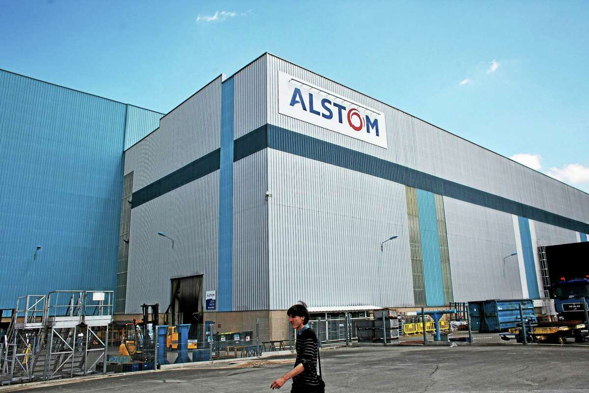 A man walks in front of the Alstom plant in Belfort, eastern France, Tuesday, June 24, 2014.