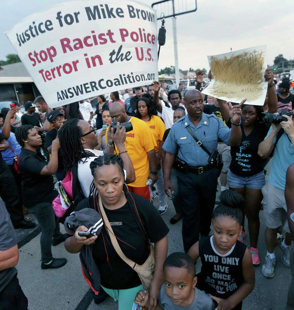 In this Aug. 16, 2014 photo, Missouri Highway Patrol Capt. Ron Johnson walks among people protesting the police shooting death of Michael Brown in Ferguson, Mo.