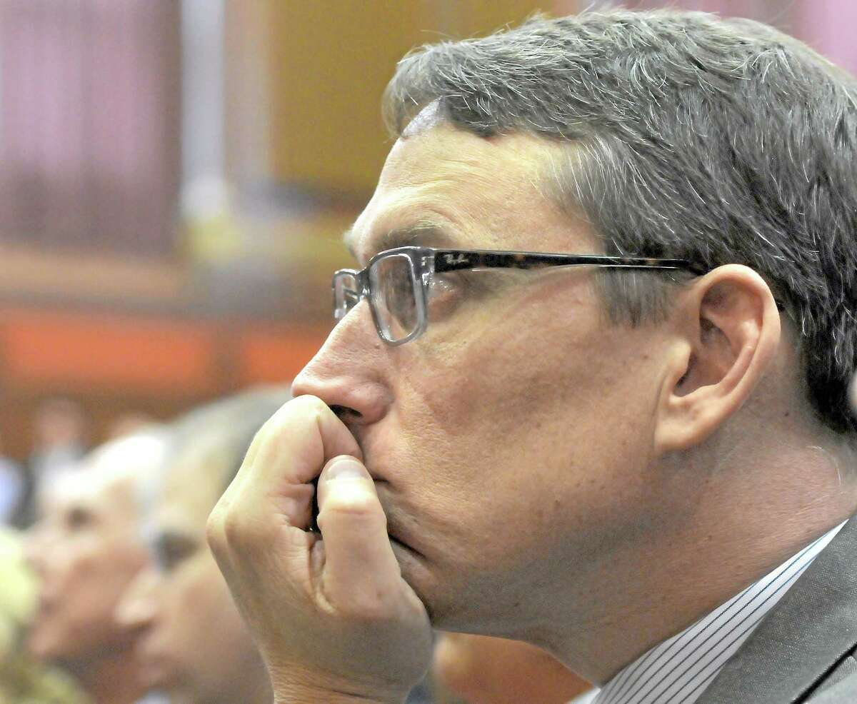 File photo: Office of Policy and Management Secretary Ben Barnes listens to Gov. Dannel P. Malloy address the CT legislature in his biennial budget address.