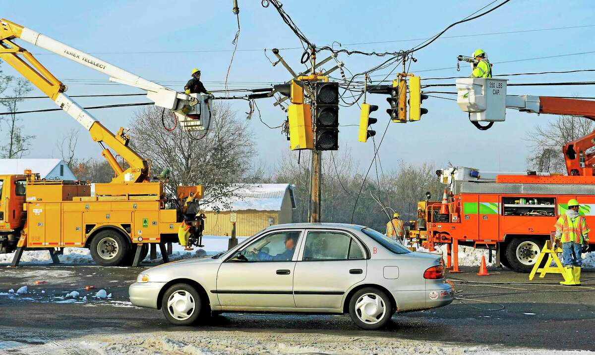 In this Oct. 31, 2011 photo, a vehicle passes under a traffic light damaged by a storm in South Windsor, Conn. The state's largest electrical utility collaborated with the University of Connecticut to open the Eversource Energy Center at UConn, devoted to studying ways to better predict and prepare the state's power infrastructure for natural disasters.