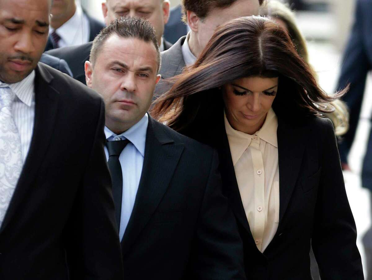"In this Oct. 2, 2014 photo, ""The Real Housewives of New Jersey"" stars Giuseppe ""Joe"" Giudice, center, and his wife, Teresa Giudice, right, of Montville Township, N.J., walk toward the Martin Luther King Jr. Courthouse before a court appearance, in Newark, N.J. A lawyer for Teresa Giudice tells The Record she will be released Wednesday, Dec. 23, 2015, from the Danbury Federal Correctional Institution in Connecticut. She will then head home to her husband and four daughters in Montville, where she will be on home confinement until Feb. 5."