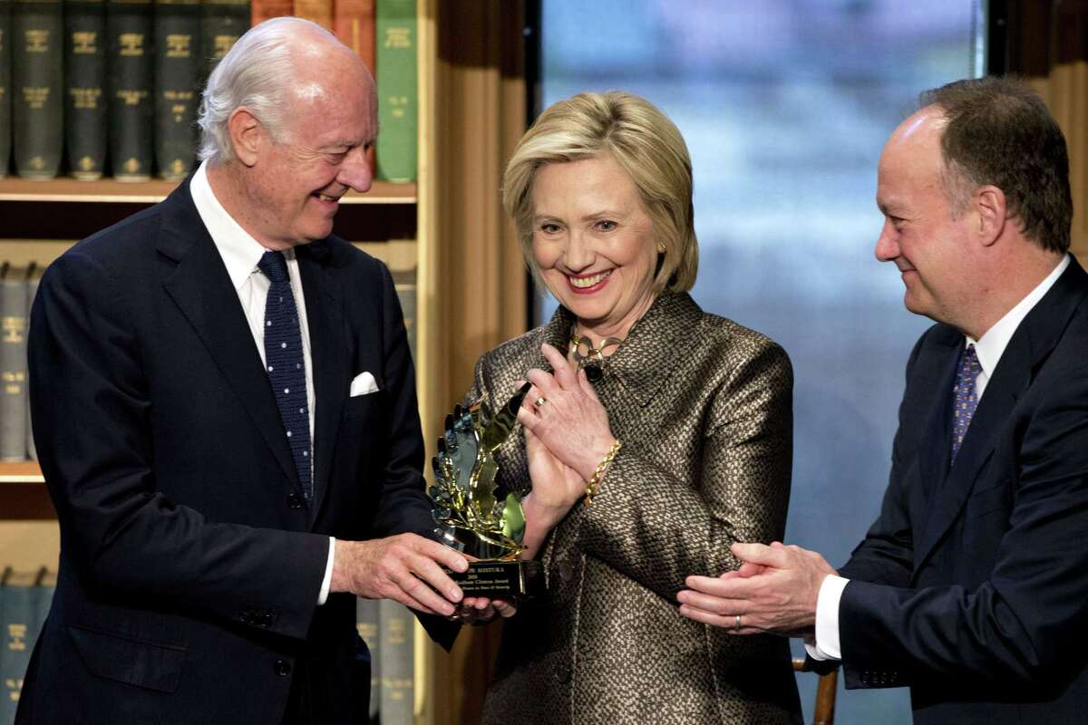 Democratic presidential candidate Hillary Rodham, center, smiles as she presents former UN Envoy for Afghanistan, and current UN Special Envoy for Syria, Staffan de Mistura, left, with a Hillary Rodham Clinton Award for Advancing Women in Peace and Security, for his work helping women in Afghanistan.