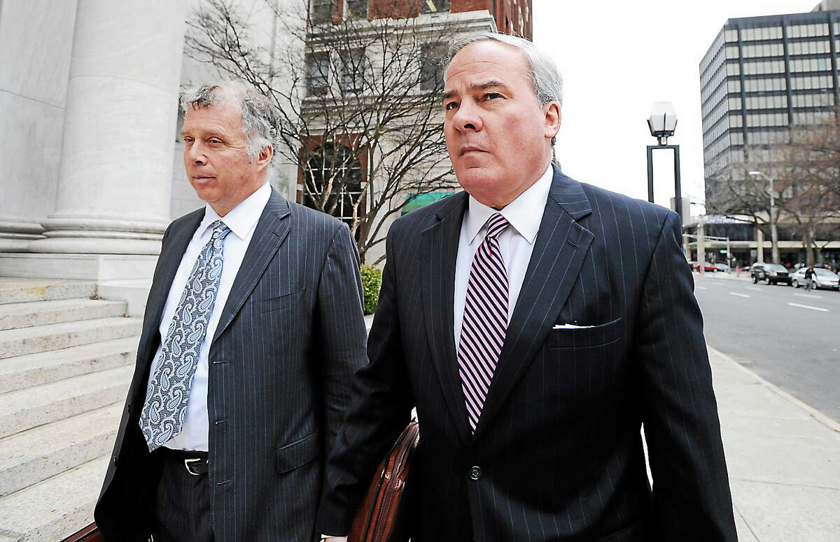 Former Connecticut Gov. John G. Rowland arrives with attorney Reid Weingarten at federal court on April 11, 2014, in New Haven, Conn. A grand jury returned a seven-count indictment alleging Rowland schemed to conceal involvement with congressional campaigns.
