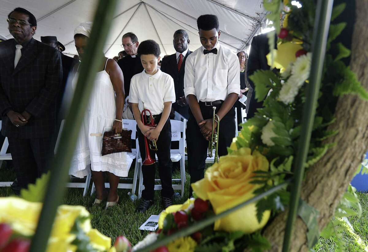 Cameron Clark, right, and Aaron Covin, second left, bow during the invocation at a wreath laying ceremony at the Hurricane Katrina Memorial, on the 10th anniversary of Hurricane Katrina in New Orleans, Saturday, Aug. 29, 2015.