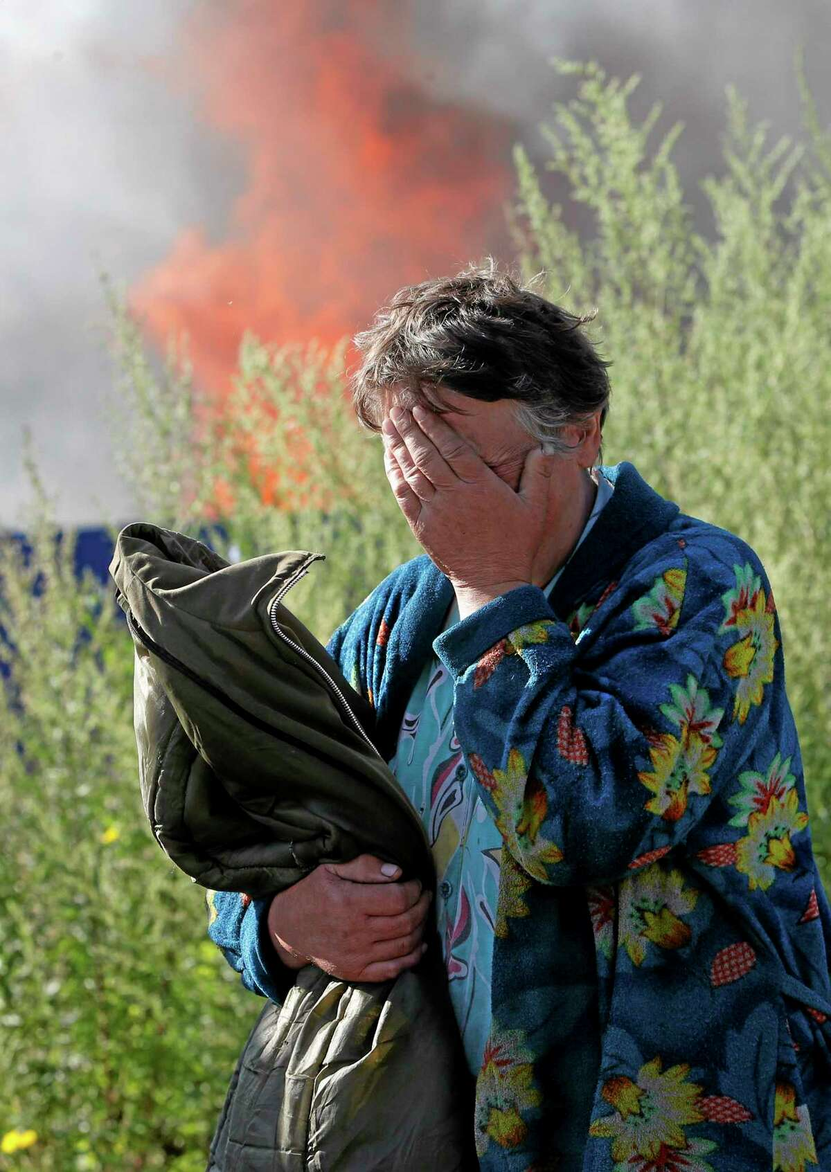 A woman cries near her burning house after shelling in the city of Slovyansk, Donetsk Region, eastern Ukraine, Monday, June 30, 2014. Residential areas came under shelling on Monday morning from government forces. (AP Photo/Dmitry Lovetsky)