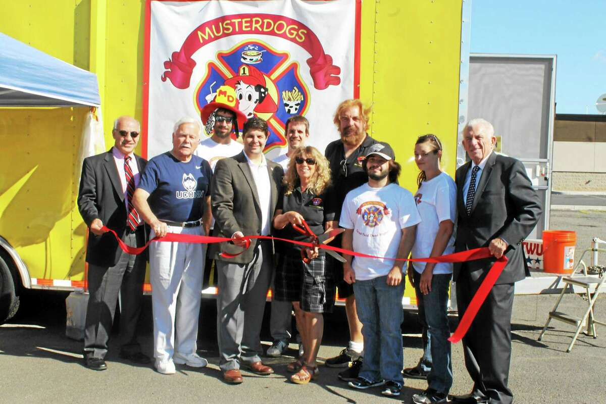Chamber President Larry McHugh (far right) and Mayor Dan Drew (center) help Musterdogs owners Sharon Paddock (center with scissors) and Joe Dinegar (rear) celebrate the grand opening of the Food Truck and Food Stand Aug. 27. Other members of the Musterdogs team are also pictured, as is Middletown Small Business Development Center Counselor Paul Dodge and Middletown Economic Development Specialist Tom Marano.