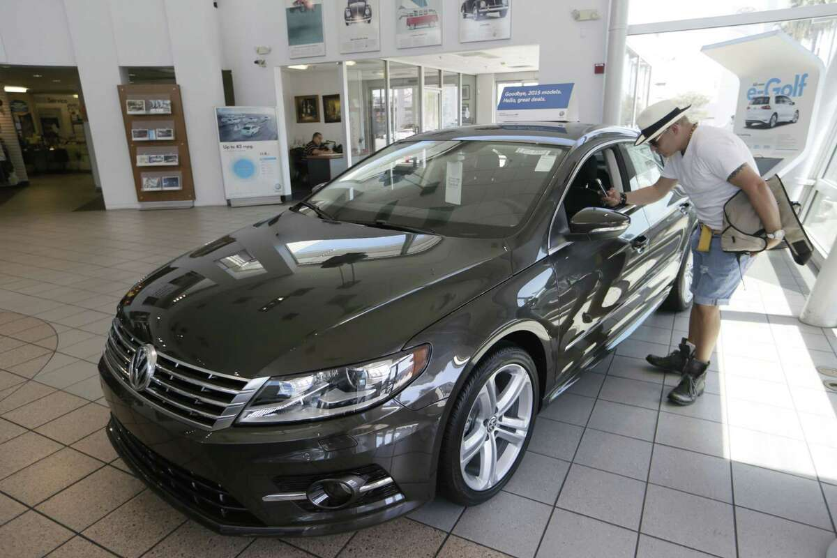 A customer checks the interior of a 2015 Volkswagen CC sports car for sale at the New Century Volkswagen dealership in Glendale, Calif.