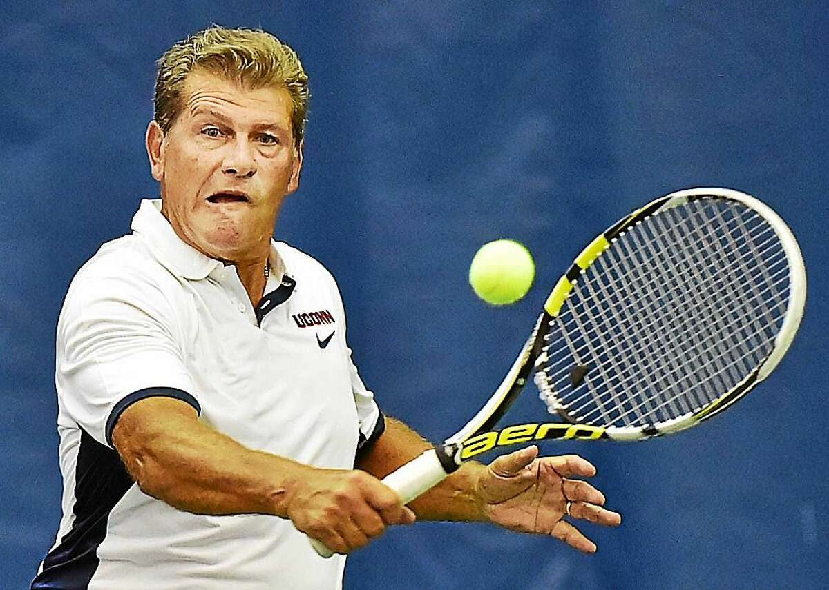 UConn women's basketball coach Geno Auriemma returns a backhand to John McEnroe during a doubles match Friday afternoon at the Cullman-Heyman Tennis Center at Yale.