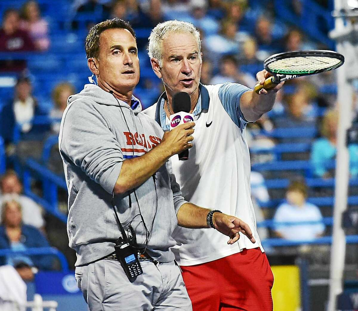 John McEnroe, with help from emcee and Tennis Channel host Andrew Krasny, raffles off two of his racquets, raising $7,000 for the Smilow Cancer Hospital at Yale-New Haven on Friday night during the men's legends match against Jim Courier at the Connecticut Tennis Center.
