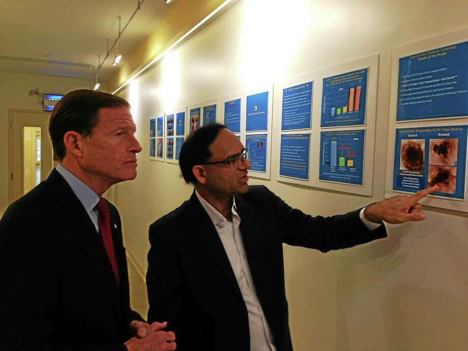 Anil Diwan, right, president and chairman of NonoViricides of West Haven and Shelton, describes the company's progress on an Ebola cure to U.S. Sen. Richard Blumenthal, D-Conn. Photo: (Ed Stannard--New Haven Register)