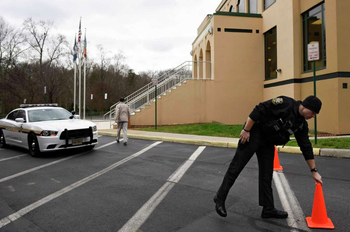 Deputy Sullivan of the Loudoun County Sheriff's Department moves a traffic cone at the All Dulles Area Muslim Society (ADAMS) Center in Sterling, Va., Friday, Dec. 18, 2015. At ADAMS, one of the largest Muslim congregations in the country, the security guards resigned, saying they felt they could no longer protect the mosque amid the anti-Muslim uproar, ADAMS board chairman Rizwan Jaka said. The guards have been replaced with a more experienced team and the center's leaders are trying to reassure worshippers worried about the risks of attending Friday prayers.
