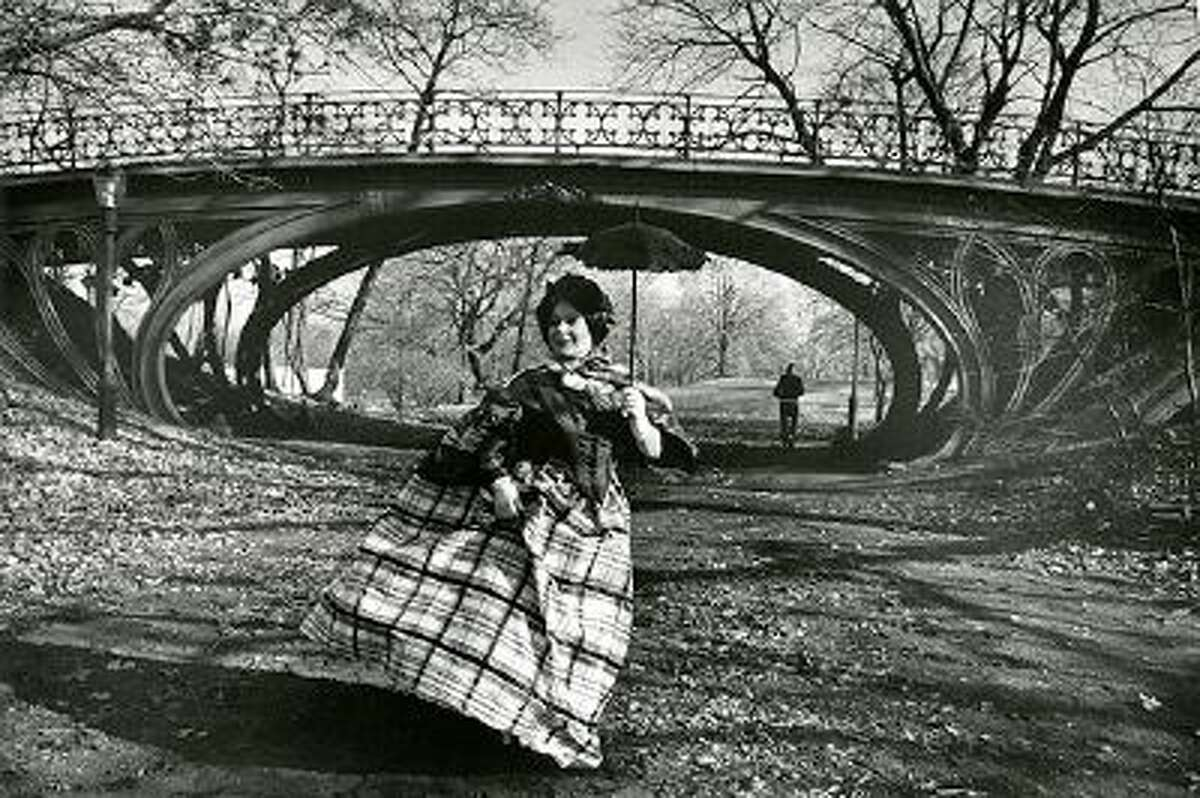 This photo provided by the New-York Historical Society shows the photographer Bill Cunningham's muse Editta Sherman in front of the Gothic bridge in Central Park, which was designed in 1860, in New York. The photo is one of 88 prints from Bill Cunningham's 1976-1978 project,