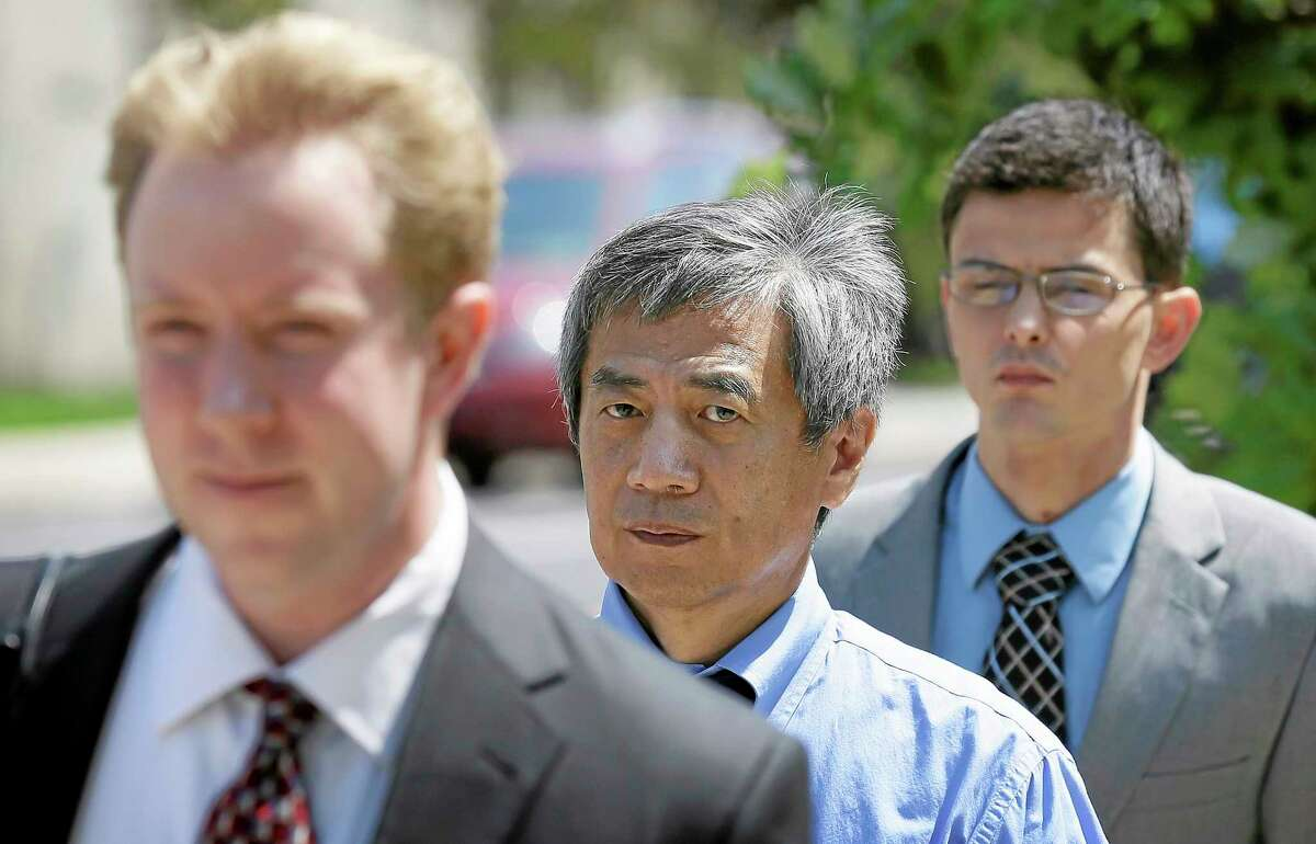 Former Iowa State University researcher Dong-Pyou Han, center, leaves the federal courthouse with his attorney Joe Herrold, left, Tuesday, July 1, 2014, in Des Moines, Iowa. Han was making his initial court appearance on charges that he falsified data to make a proposed AIDS vaccine appear promising and win millions of dollars in federal grant money. (AP Photo/Charlie Neibergall)