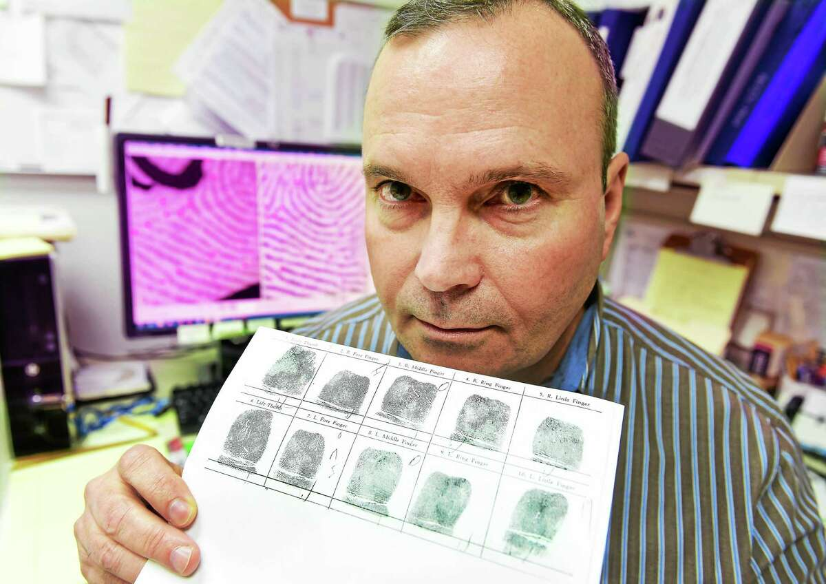 PETER HVIZDAK — NEW HAVEN REGISTER John Brunetti, with a copy of fingerprints, is the supervisor of the Latent Print Unit of the state Department of Emergency Services and Public Protection, Division of Scientific Services in Meriden.