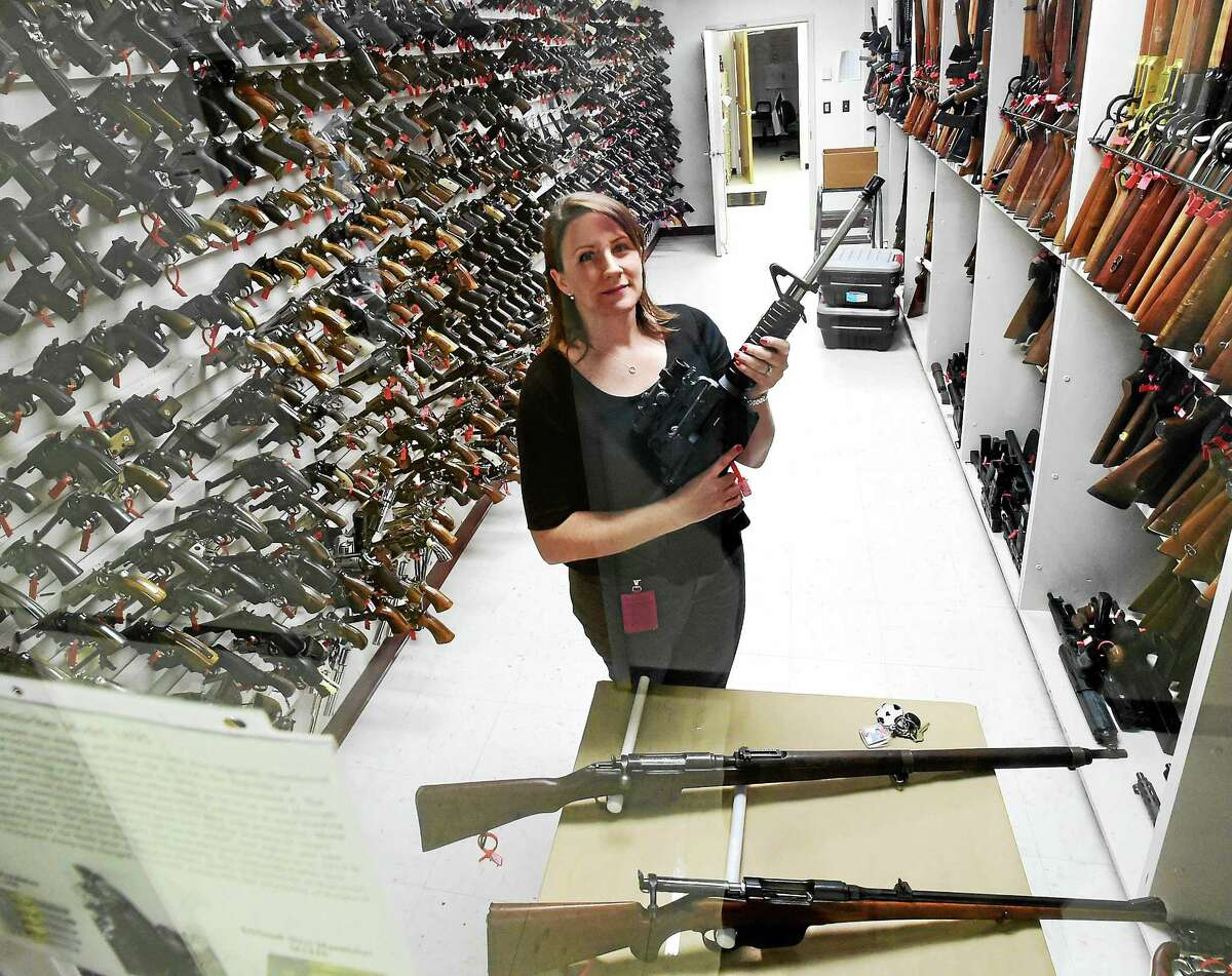 PETER HVIZDAK — NEW HAVEN REGISTER Jill Therriault, forensic science examiner of the Firearms Identificatiion Unit in the firearms reference collection room at the state Department of Emergency Services and Public Protection, Division of Scientific Services in Meriden.