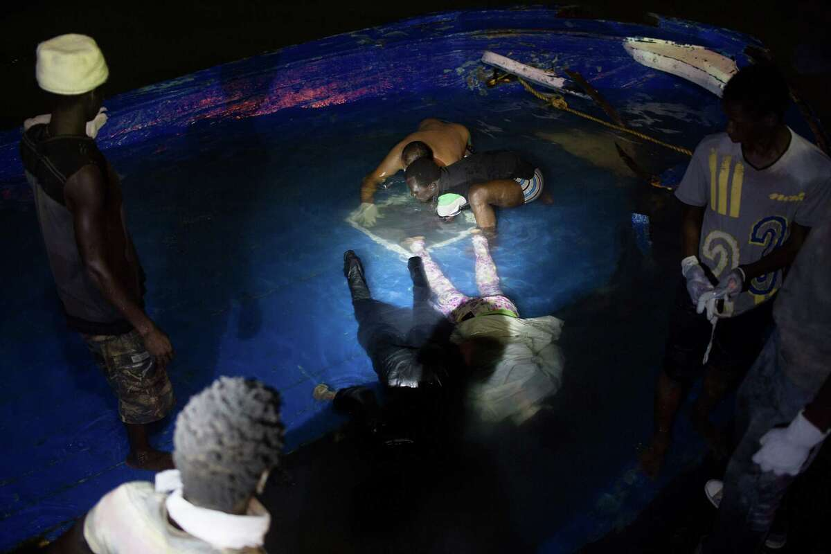 In this Thursday, Aug. 27, 2015, photo, bodies of migrants are pulled from a hole in the deck after their boat sank off the coast of in Zuwara, Libya. It was not clear how many migrants drowned. Dozens of boats are launched from lawless Libya each week, with Italy and Greece bearing the brunt of the surge.