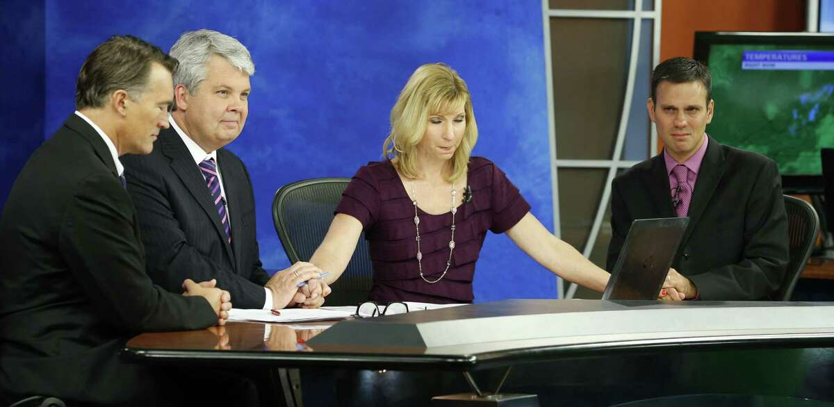 WDBJ-TV7 news morning anchor Kimberly McBroom, second from right, and meteorologist Leo Hirsbrunner, right, are joined by visiting anchor Steve Grant, second from left, and Dr. Thomas Milam, of the Carilion Clinic, as they observe a moment of silence during the early morning newscast at the station, in Roanoke, Va., Thursday. The moment of silence was at the moment reporter Alison Parker and cameraman Adam Ward were killed during a live broadcast Wednesday.
