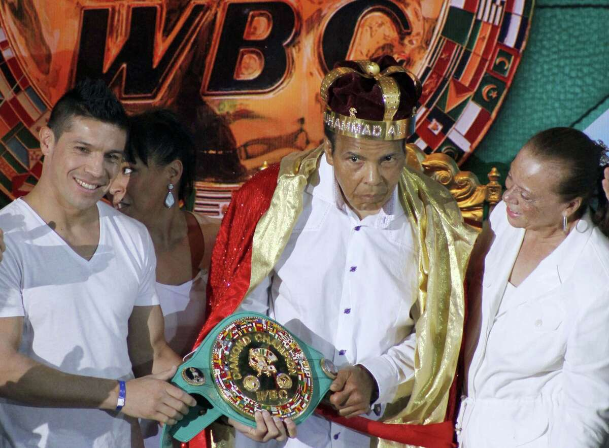 """In this Monday, Dec. 3, 2012 photo, the former heavyweight boxing champion Muhammad Ali, center, is crowned """"King of Boxing"""" while accompanied by his wife, Lonnie, right, and Argentine boxer Sergio Martinez during the 50th convention of the World Boxing Council in Cancun, Mexico."""