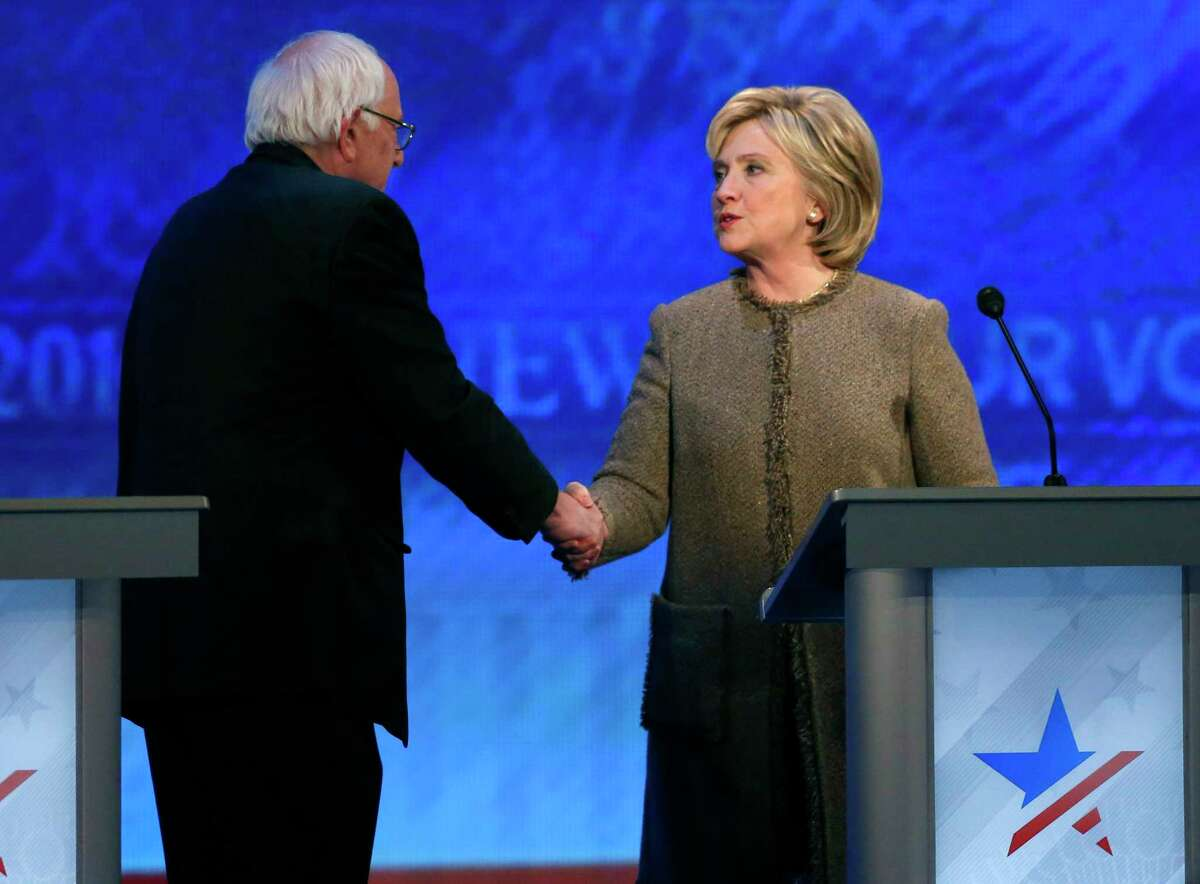 Bernie Sanders, left, speaks to Hillary Clinton after a Democratic presidential primary debate Saturday, Dec. 19, 2015, at Saint Anselm College in Manchester, N.H.