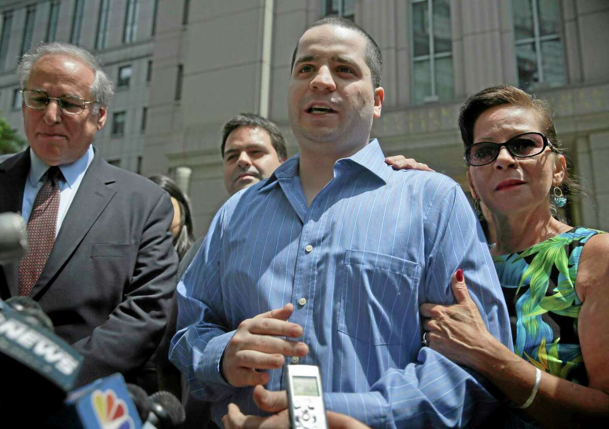 GIlberto Valle, center, makes a short statement to the assembled media as he leaves Manhattan federal court in New York, Tuesday, July 1, 2014. A federal judge has overturned the conviction of Valle, a former New York City police officer accused of plotting to kidnap, kill and eat young women. Valle's mother, Elizabeth Valle is at right. (AP Photo/Seth Wenig)