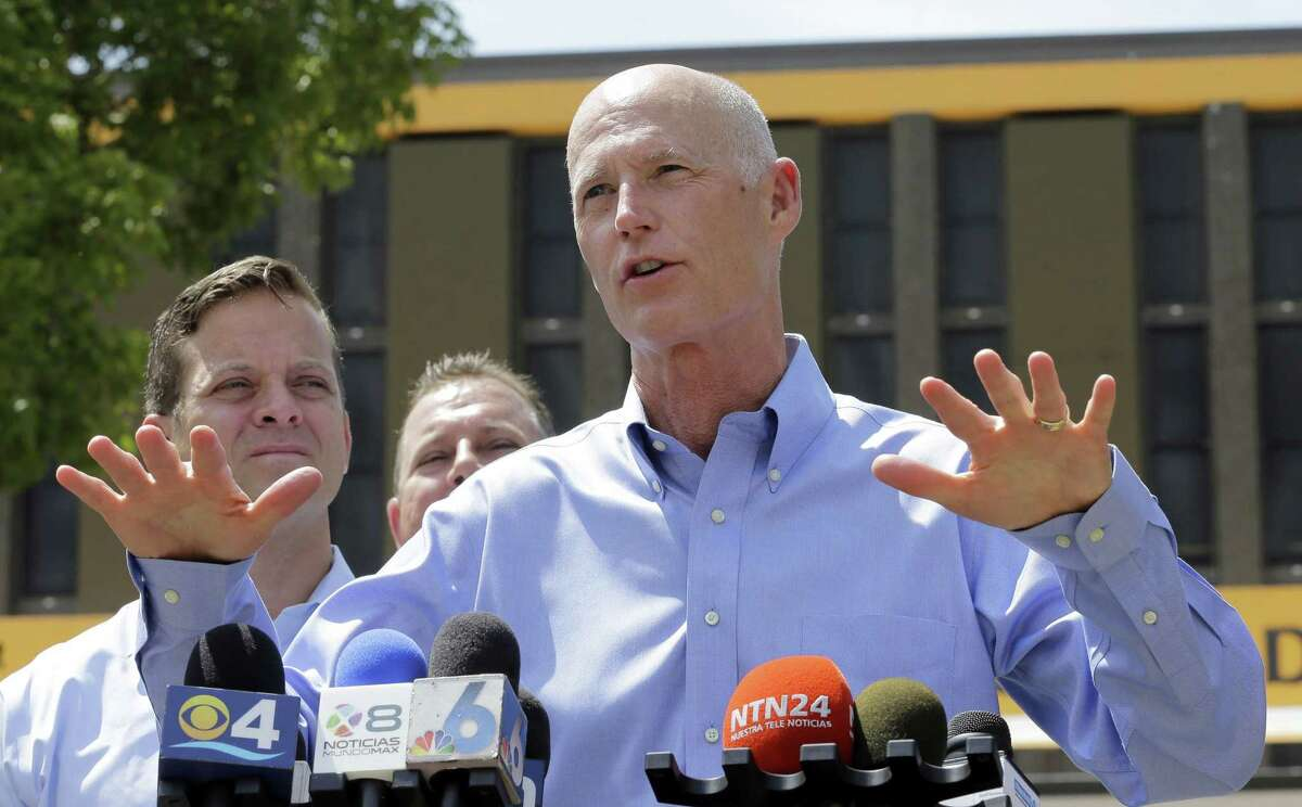 """Gov. Rick Scott, right, talks to reporters at the Miami-Dade State Emergency Operations Center as Lt. Gov. Carlos Lopez-Cantera, left, looks on Friday, Aug. 28, 2015, in Doral, Fla. Gov. Rick Scott said Friday that Tropical Storm Erika poses a """"severe threat to the entire state"""" and declared state of emergency. Scott made his declaration shortly after forecasters adjusted the trajectory of the storm to show that it's predicted to strike the southern tip of the state and then traverse northward."""