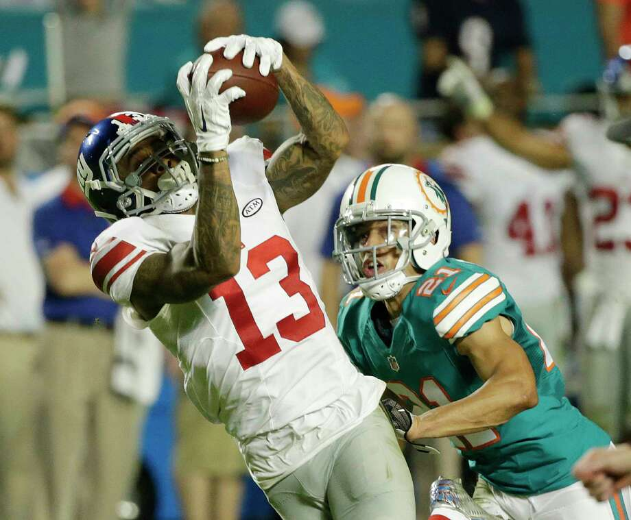 New York Giants wide receiver Odell Beckham (13) makes a catch as Miami Dolphins cornerback Brent Grimes (21) defends, during the first half of an NFL football game, Monday, Dec. 14, 2015, in Miami Gardens, Fla.  (AP Photo/Wilfredo Lee) Photo: AP / AP