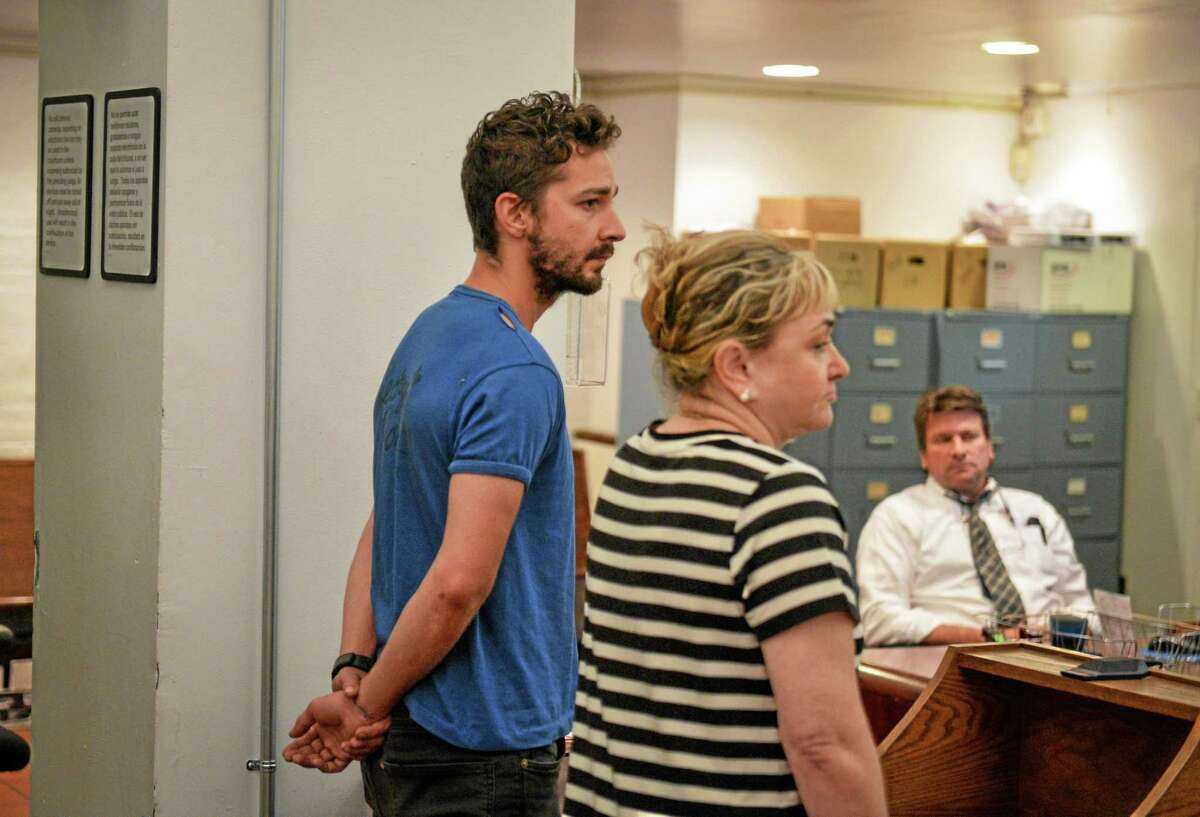 Shia LaBeouf, left, represented by a Legal Aid attorney, is arraigned in Midtown Community Court, in New York, Friday, June 27, 2014. LaBeouf was released from police custody Friday after he was escorted from a Broadway theater for yelling obscenities and continued to act irrationally while being arrested, authorities said. He's due back in court July 24. (AP Photo/Anthony DelMundo, NY Daily News, Pool)