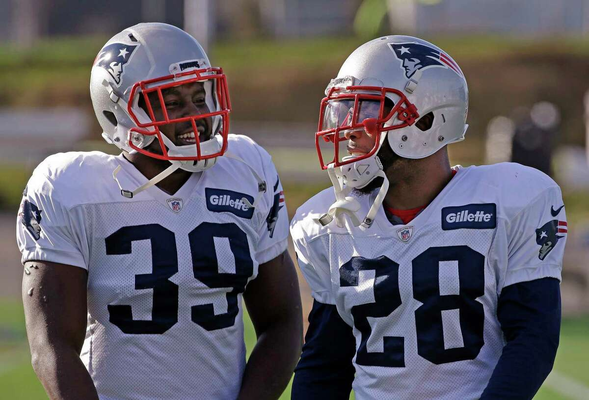 New England Patriots newly acquired running back Montee Ball (39) and running back James White (28) talk during a stretching session before practice begins at the NFL football team's facility Wednesday, Dec. 16, 2015, in Foxborough, Mass. (AP Photo/Stephan Savoia)
