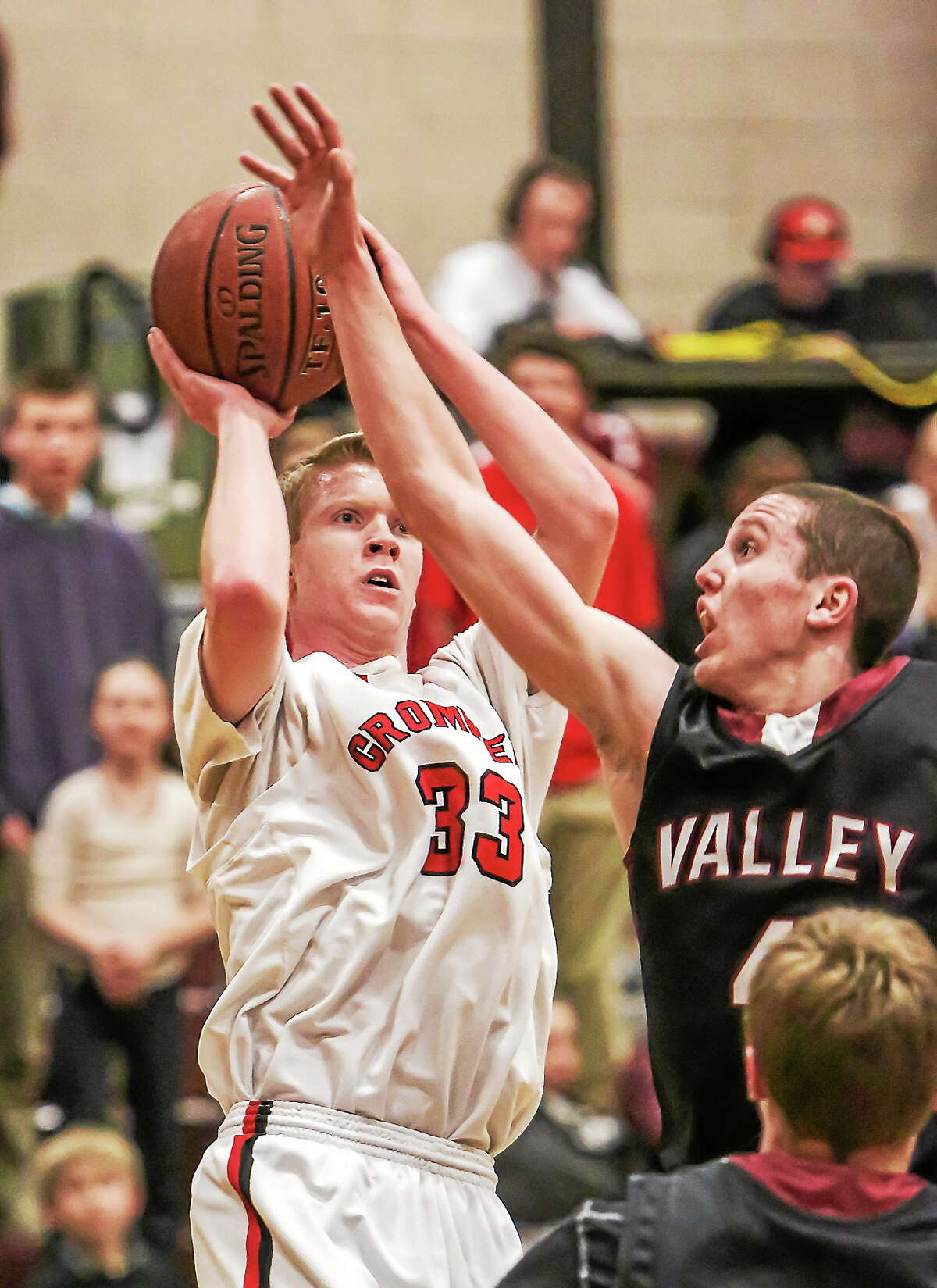 Cromwell's Jake Regula shoots a 3-pointer attempt while being defended by Valley Regional's David Bradbury.